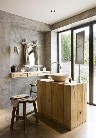 Béton ciré sur les murs et le sol combiné à des touches de bois données par un îlot central et des tabouret, voilà une salle de bain ultra déco et originale !