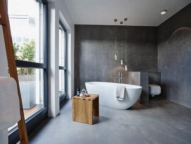 Déco zen et style épuré dans la salle de bain avec les murs et le sol en béton ciré, une baignoire îlot, un tabouret en bois et des suspensions lumineuses originales